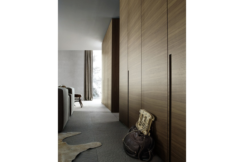 Poliform Madison wardrobe with doors in canaletto walnut with integrated vertical handle detail